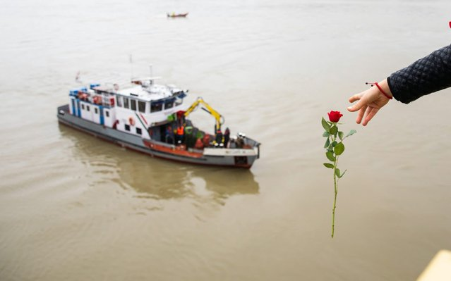 A woman throws a flower from the Margaret Bridge during the search operation on the River Danube in Budapest, Hungary, 30 May 2019, following a collision of a hotel ship and a smaller cruise ship on the previous evening. The cruise ship sank with thirty-three South Korean passengers and two Hungarian staff on board. At least seven people died and nineteen are missing. The shipwreck has been found at Margaret Bridge. (Photo by Balazs Mohai/EPA/EFE/Rex Features/Shutterstock)