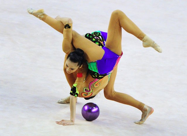 Gold medalist China's team perform their exercise with 3 balls and 2 ribbons at the team final during the Rhythmic Gymnastics World Cup in Debrecen, Hungary on March 16, 2014. (Photo by Attila Kisbenedek/AFP Photo)