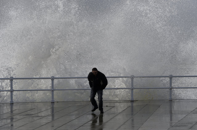 A man reacts as waves crash against the seafront of San Lorenzo beach in Gijon, northern Spain, February 28, 2017. (Photo by Eloy Alonso/Reuters)