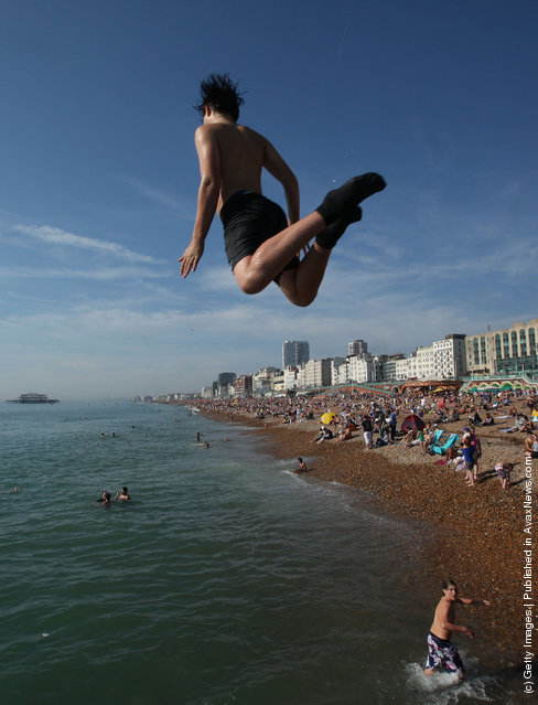 A youth jumps into the water from a sea wall