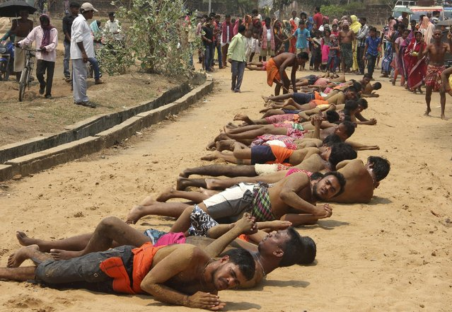 Devotees roll on the ground to reach a temple as part of a ritual during the Danda festival at Mandhashal village in Khordha district of the eastern state of Odisha, India, April 12, 2016. Hundreds of male devotees participate in the ritual to appease Hindu god Shiva and goddess Kali during Danda, or the festival of penance. (Photo by Reuters/Stringer)