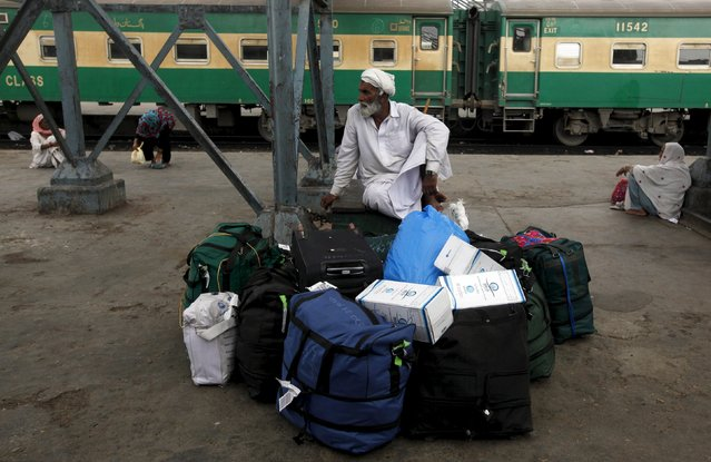 A man sits with his belongings while waiting for a train to leave for his hometown, at Cantonment Railways Station in Karachi, Pakistan, May 25, 2015. (Photo by Akhtar Soomro/Reuters)