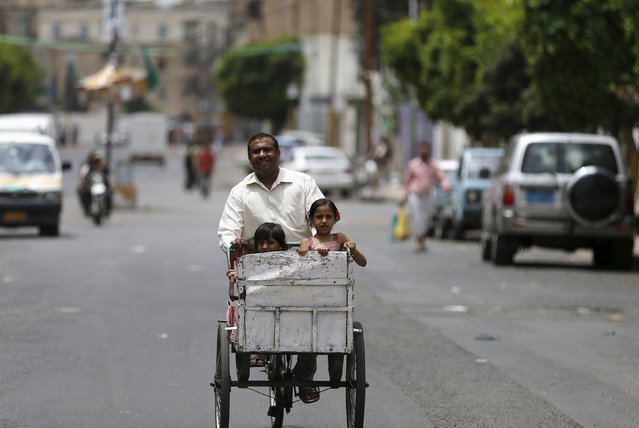 A man travels with his children on a rickshaw in Yemen's capital Sanaa May 7, 2015. (Photo by Khaled Abdullah/Reuters)