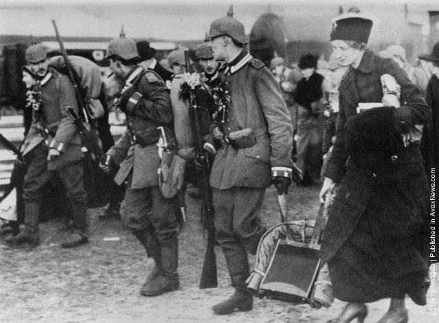 1914: German soldiers marching to the front during the first World War.  A woman helps one man with his pack