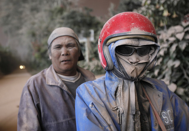 Motorists are seen covered in volcanic ash from the eruption of Mount Sinabung, in Suka Tepu, North Sumatra, Indonesia, Saturday, June 13, 2015. The volcano, which was put on it highest alert level last week, has sporadically erupted since 2010 after being dormant for 400 years. (AP Photo/Binsar Bakkara)