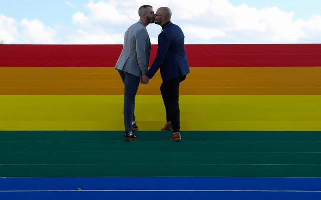 Daniel Diaz and Juan Jose Acosta, both from Brooklyn, kiss during an engagement photo shoot on a giant LGBTQ Pride Flag installed on the steps of Franklin D. Roosevelt Four Freedoms State Park to celebrate WorldPride in New York City, U.S., June 14, 2019. (Photo by Andrew Kelly/Reuters)