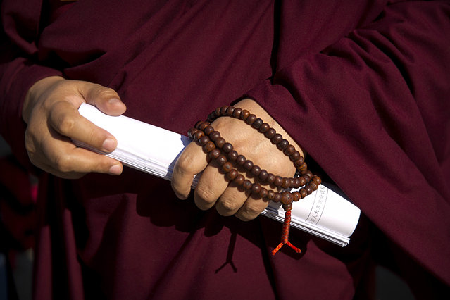 In this Wednesday, March 8, 2017 photo, a Tibetan delegate wears prayer beads and carries rolled-up paperwork as he arrives for a plenary session of China's National People's Congress (NPC) at the Great Hall of the People in Beijing. (Photo by Mark Schiefelbein/AP Photo)