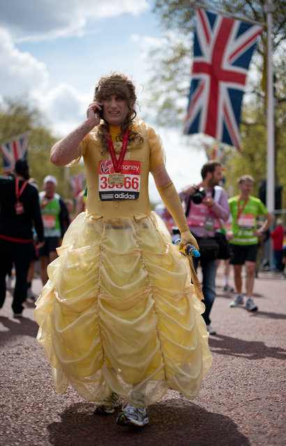 A man in a dress recovers after crossing the finish line of the 2012 London Marathon on April 22, 2012. (Photo by Leon Neal/AFP Photo)