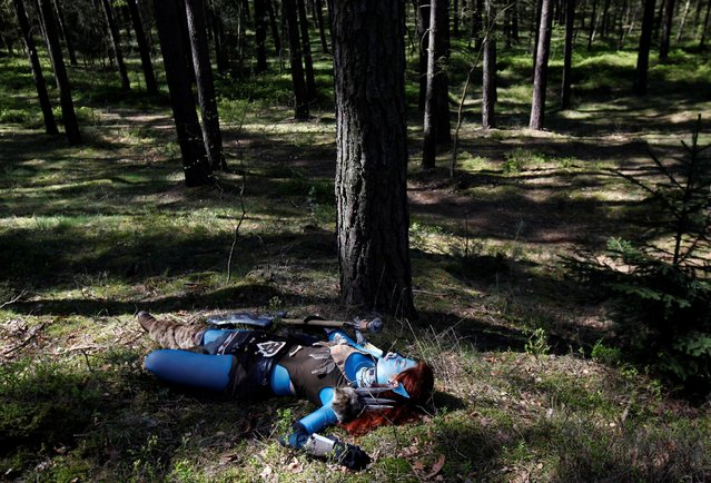 """A woman dressed as a character from the computer game """"World of Warcraft"""" lies on the ground in a forest near the village of Sosnova, Czech Republic, April 30, 2016. (Photo by David W. Cerny/Reuters)"""