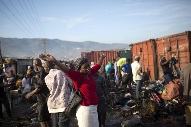 A woman stands next to to a pile a fire damaged clothing after a massive fire at a market in Port-au-Prince, Haiti, Monday March 20, 2017. The fire raged at the biggest central market in the center of the Capital. (Photo by Dieu Nalio Chery/AP Photo)