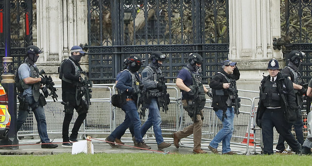 Armed police officers enter the Houses of Parliament in London, Wednesday, March 22, 2017 after the House of Commons sitting was suspended as witnesses reported sounds like gunfire outside. (Photo by Kirsty Wigglesworth/AP Photo)