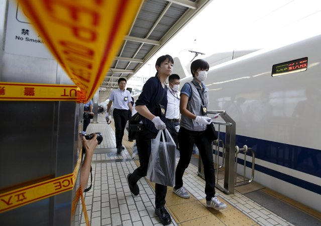 Police officers carry passengers' personal belongings as they collect these from a Shinkansen bullet train at Odawara station after it made an emergency stop, in Odawara, west of Tokyo June 30, 2015. (Photo by Toru Hanai/Reuters)