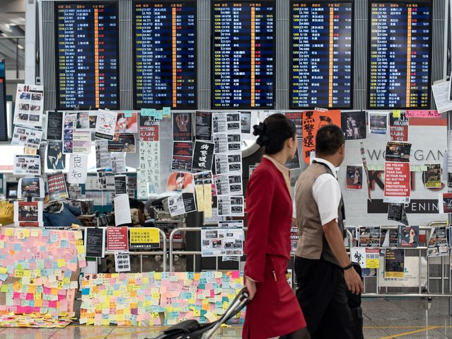 Two flight attendants walk past an electric display board covered with memos and posters at Hong Kong's international airport on August 13, 2019, the day after the airport closed due to pro-democracy protests. Hong Kong airport re-opened on August 13 after a rally the day before by thousands of pro-democracy protesters triggered an unprecedented shutdown, but hundreds of flights were still listed as cancelled. (Photo by Philip Fong/AFP Photo)