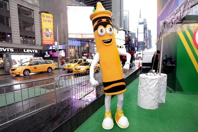 """A dandelion crayon character poses for photos during a Crayola event in New York's Times Square, Friday, March 31, 2017. Crayola announced Friday, National Crayon Day, that it's replacing the color dandelion in its 24-pack with a crayon in """"the blue family"""". (Photo by Richard Drew/AP Photo)"""