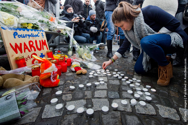 A woman lights candles as people react to yesterday's gun and grenade attack in central Liege