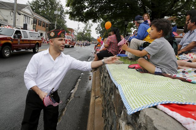 A member of the Veterans of Foreign Wars hands out U.S. flags to spectators at the Independence Day Parade in Fairfax, Virginia July 4, 2015. Americans marched in star-spangled parades, ran relay races, gathered for fireworks shows and crowned a new world hot dog eating champion as they celebrated Independence Day in traditional style on Saturday. (Photo by Jonathan Ernst/Reuters)