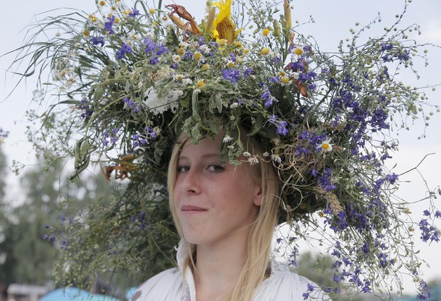 A girl with a ritual garland on her head poses for a photograph during a traditional Midsummer Night celebration, near the capital Kiev, Ukraine, Monday, July 6, 2015. (Photo by Efrem Lukatsky/AP Photo)