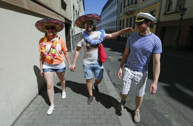"""Carnival revellers walk in the street during the postponed """"Rosenmontag"""" (Rose Monday) parade in Mainz, Germany, May 8, 2016, after the original parade in February was cancelled due to severe weather. (Photo by Ralph Orlowski/Reuters)"""