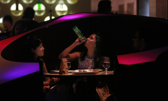 """In this Wednesday, April 2, 2014 photo, an Indian woman drinks with her friend at a night club """"blueFROG"""" in Mumbai, India. As India begins its weekslong election process Monday, April 7, the enormous population of ambitious, tech-savvy and politically engaged youths has more potential than ever to sway the outcome. More than 378 million of India's 814 million eligible voters between 18 and 35, according to census records. (Photo by Rafiq Maqbool/AP Photo)"""
