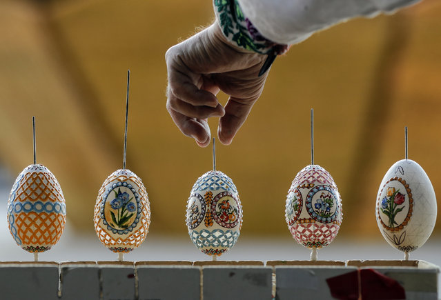 In this Thursday, April 13, 2017, picture artisan Nicu Poenariu turns Easter eggs on sale at a fair in Bucharest, Romania. (Photo by Vadim Ghirda/AP Photo)