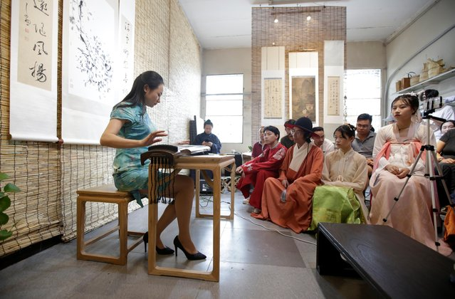 """Young people dressed in """"Hanfu"""", or Han clothing, attend a performance of the """"guqin"""" traditional musical instrument at an art space in Beijing, China, August 18, 2019. What keeps people reaching for their Hanfu outfits is often more personal. Since starting to wear Hanfu, Li Doudou said she has attended a class on traditional tea ceremonies. She is also planning to learn to play the """"guqin"""", an ancient seven-stringed zither. (Photo by Jason Lee/Reuters)"""