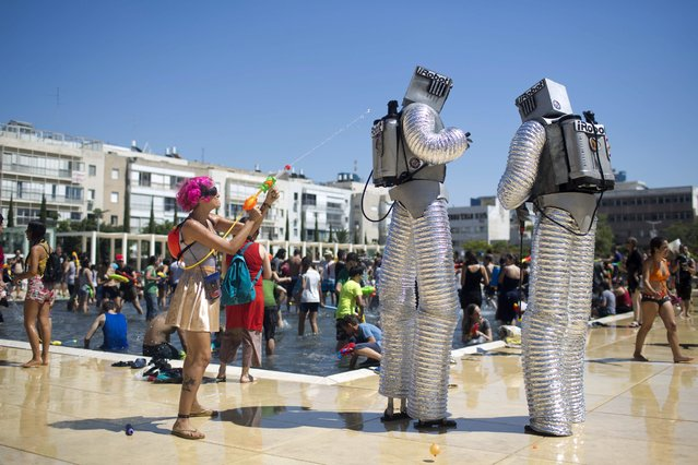 Israelis in costumes spray water on each other during the annual Tel Aviv Water War on Hbima Square in Tel Aviv, Israel,10 July 2015. The annual water fight is on his 11th edition. (Photo by Abir Sultan/EPA)