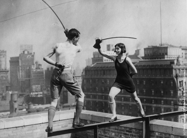 1925: Star and Isabelle Jones, of the famous theatrical Jones family, fencing on the edge of the roof of the skyscraper, Times Square Hotel