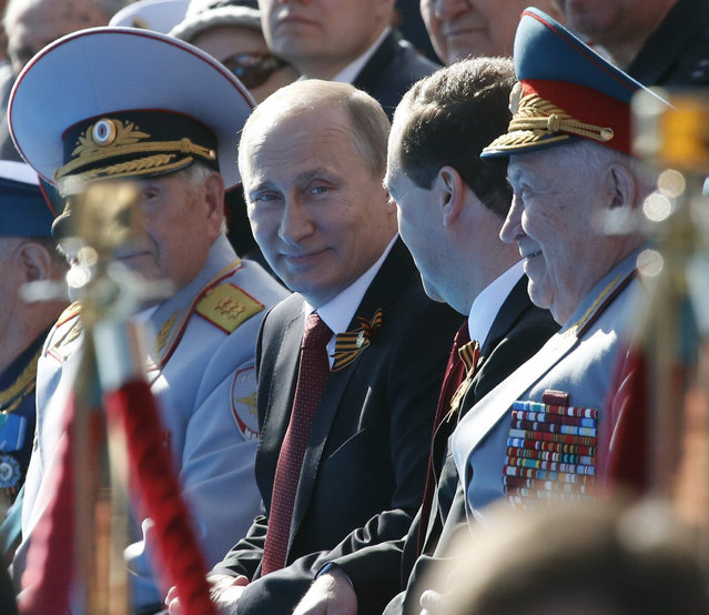Russia's President Vladimir Putin (2nd L) speaks with Prime Minister Dmitry Medvedev (2nd R) after arriving to watch the Victory parade in Moscow's Red Square May 9, 2014. (Photo by Grigory Dukor/Reuters)
