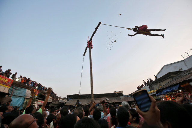 """A Hindu devotee hangs from a rope and throws offerings for people to catch during the """"Chadak"""" ritual, which is held to worship the Hindu deity Lord Shiva, in Kolkata, April 14, 2017. (Photo by Rupak De Chowdhuri/Reuters)"""