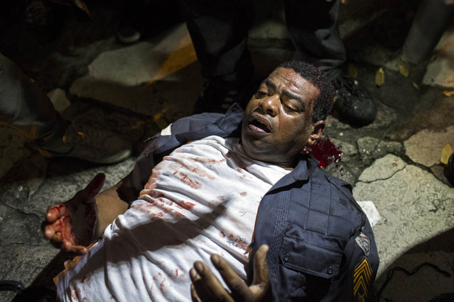 A policeman lies injured on the ground after clashing with demonstrators during a protest in Rio de Janeiro, Brazil, Monday, June 17, 2013. (Photo by Felipe Dana/AP Photo)