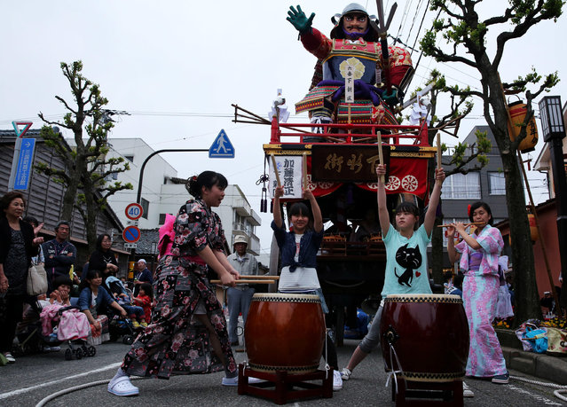 Japanese girls perform Taiko drum front of the huge paper doll cart of historical figure named Katoh Kiyomasa during the Mikuini annual festival on May 20, 2014 in Sakai, Japan. The annual festival takes place from May 19-21 and is attended by thousands of visitors. During the festival people dressed in traditional Japanese costumes pull carts carrying 6 meter high dolls of Japanese historical figures through the narrow streets. The origins of the festival are unclear but its history can be traced back more than 250 years. (Photo by Buddhika Weerasinghe/Getty Images)