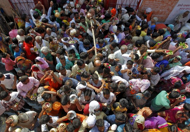 Devotees of Hindu god Shiva carrying pots filled with water from the Ganges river and other religious offerings wait for their turn to worship at Padilla Mahadev temple in Allahabad, India, July 13, 2015. (Photo by Jitendra Prakash/Reuters)
