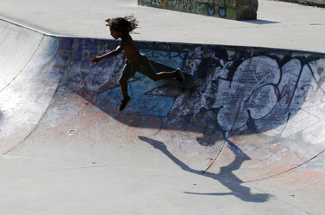 In this July 9, 2015 photo, a young skater falls as he plays in a skate park in Milan, Italy. (Photo by Antonio Calanni/AP Photo)