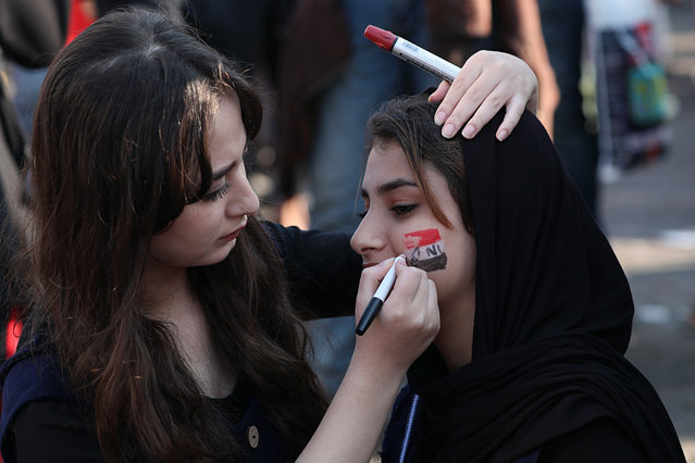A protester gets her face painted with the colors of the Iraqi flag during ongoing anti-government protests at Tahrir square in Baghdad, Iraq, Thursday, October 31, 2019. (Photo by Hadi Mizban/AP Photo)