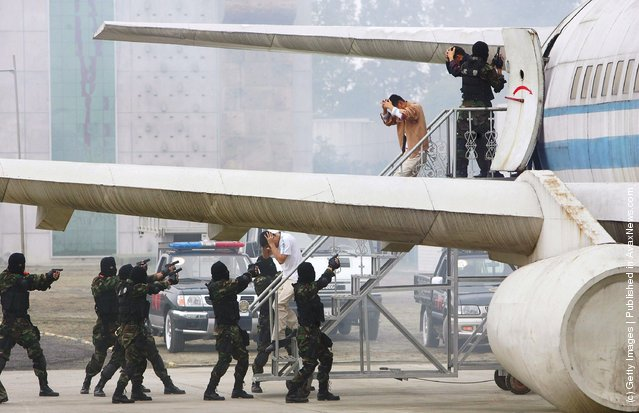 Chinese anti-hijacking special policemen participate in an anti-terror drill at a training base of Chengdu Armed Police Headquarters