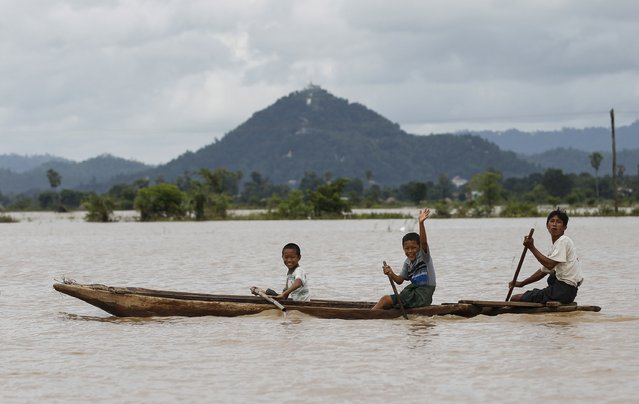 People wave from their boat along a flooded rice field in Kawlin township, Sagaing division, Myanmar, July 21, 2015. (Photo by Soe Zeya Tun/Reuters)