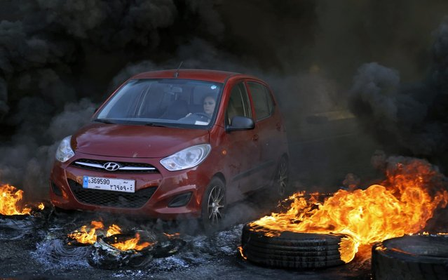 A woman drives through burning tires blocking a highway in Lebanon's northern port city of Byblos (Jbeil) during ongoing anti-government demonstrations on November 4, 2019. Demonstrators in Lebanon tried to block key roads Monday after a weekend of mass rallies confirmed that political promises had failed to extinguish the unprecedented protest movement. (Photo by Joseph Eid/AFP Photo)