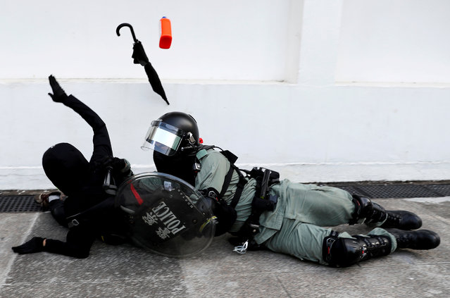 Riot police officer tries to subdue a protester during an anti-government demonstration in Hong Kong, China, November 10, 2019. (Photo by Tyrone Siu/Reuters)