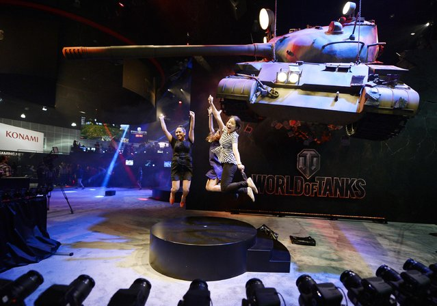"Attendees Priscilla Padilla (L-R), Sacha Tank and Stella Yeo get their picture taken in front of a mock battle tank, promoting the new multiplayer action game ""World of Tanks"", in the Ubisoft booth at the 2014 Electronic Entertainment Expo, known as E3, in Los Angeles, June 10, 2014.  REUTERS/Kevork Djansezian"