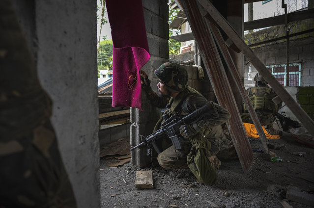 A soldier taking a look at enemy positions, while they try to clear the city of armed militants, one street at a time on May 25, 2017 in Marawi city, southern Philippines. Gun battles between ISIS-linked militants and Filipino troops erupted in Marawi city on Tuesday when gunmen from the local terrorist organizations Maute Group and Abu Sayyaf rampaged through the southern city setting buildings on fire. President Rodrigo Duterte has declared 60 days of martial law in Mindanao as thousands of residents were reported to have fled from Malawi city while at least 21 people were killed, including a police chief who had been beheaded. President Duterte said the influence of Islamic State is one of the nation's top security concerns, and martial law on Mindanao island could be extended across the Philippines to enforce order, allowing the detention of people without charges. (Photo by Jes Aznar/Getty Images)