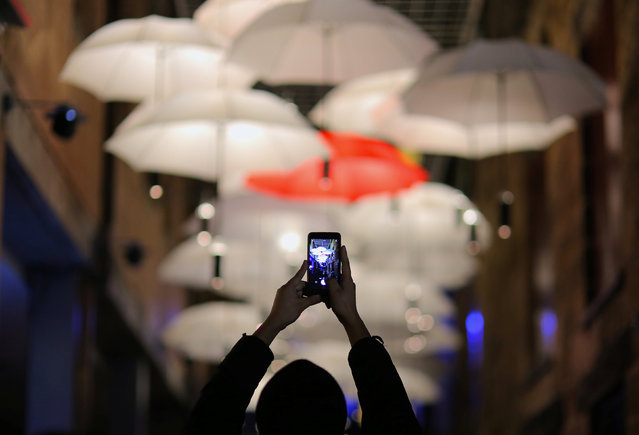 A member of the public takes a photograph of a canopy of umbrellas that are part of an installation titled 'Under My Umbrella' during the Vivid Sydney festival of light and sound in Sydney, Australia, May 27, 2017. (Photo by Steven Saphore/Reuters)