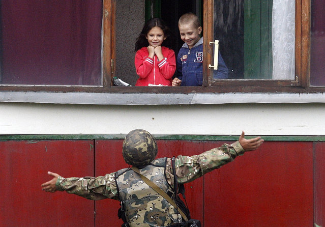 """A Ukrainian soldier gestures as he talks with children on August 18, 2014 in the small easter city of Popasna, Lugansk region, recently freed by Ukrainian forces from pro-Russia militants. Kiev accused pro-Russian rebels in eastern Ukraine of killing """"many"""" civilians trying to leave a conflict-torn area by shelling them with equipment provided by Moscow. """"Militants shot at a convoy of civilians trying to flee the conflict area not far from Lugansk... using Grad rocket launchers and mortar guns given by Russia"""", said security spokesman Andriy Lysenko. """"Many people died, including women and children"""". (Photo by Anatolii Stepanov/AFP Photo)"""