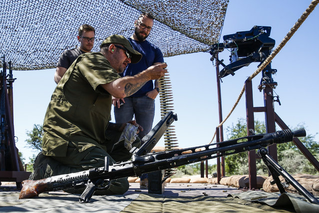 In this May 24, 2017 photo, Glenn Fleming, center, loads up an MG-42 machine gun for guests participating in an Allies and Axis all-day experience at Ox Ranch in Uvalde, Texas. The ranch is a free-roaming range filled with exotic animals, some to hunt, and home to DriveTanks.com, where tourists pay to transport themselves into another era and another life. (Photo by Michael Ciaglo/Houston Chronicle via AP Photo)