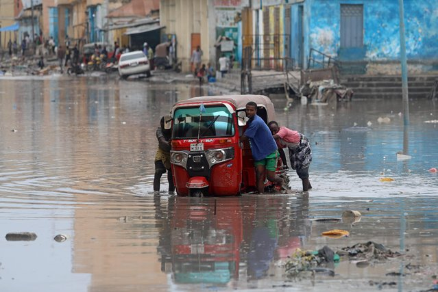 Somali men push their rickshaw through flood waters after a rainfall in Mogadishu, Somalia November 26, 2019. (Photo by Feisal Omar/Reuters)