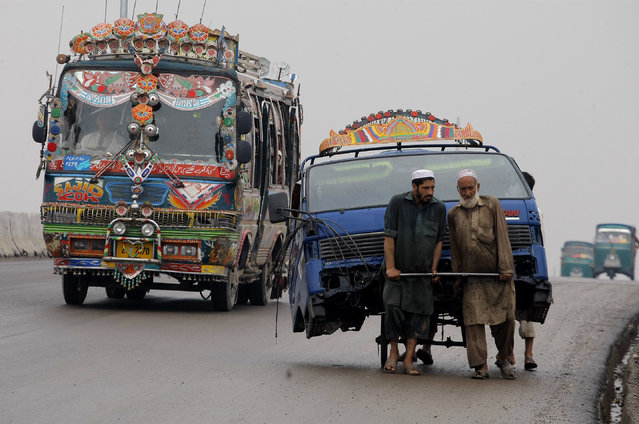 Pakistani laborers transport the front portion of a vehicle using a handcart at a road in Peshawar, Pakistan, Monday, August 3, 2015. (Photo by Mohammad Sajjad/AP Photo)