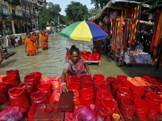 A vendor adjusts a wooden stool at her flooded roadside stall selling vermilion after heavy monsoon rains in the eastern India caused the rise in water levels of river Ganga and its tributaries in Kolkata, India, August 3, 2015. (Photo by Rupak De Chowdhuri/Reuters)