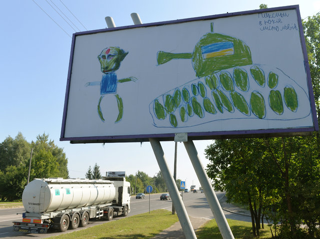 A drawing of an eight-year old Ukrainian boy, Maxim, depicting Russian President Vladimir Putin and an Ukrainian tank, is displayed on a billboard in the western Ukrainian city of Lviv on August 20, 2014. (Photo by Yurko Dyachyshyn/AFP Photo)
