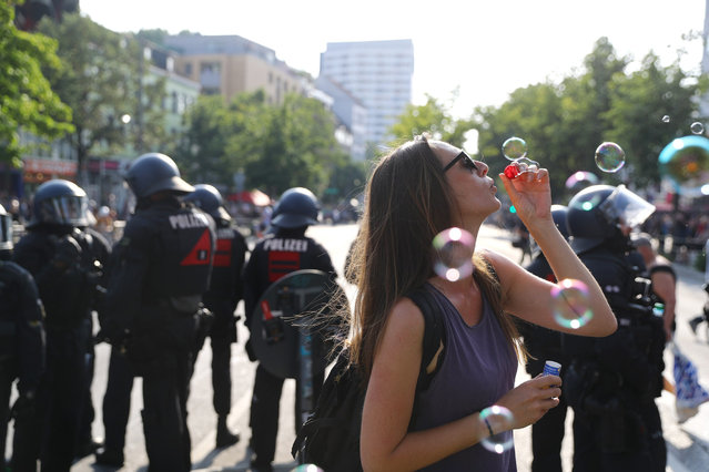 A protester blows bubbles next to German police at a demonstration during the G20 summit in Hamburg, Germany, July 7, 2017. (Photo by Kai Pfaffenbach/Reuters)