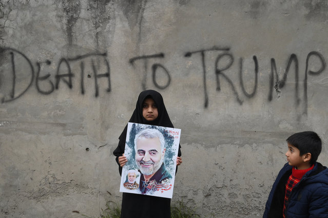 A Shiite Muslim girl holds a poster of Iranian commander Qasem Soleimani as she takes part in a anti-US protest against the killing of top Iranian commander Qasem Soleimani in Iraq, in Lahore on January 12, 2020. Iran's Revolutionary Guards chief briefed parliament on January 12 over the killing of a top general by the US, Tehran's retaliation and the subsequent downing of an airliner, ISNA news agency said. (Photo by Arif Ali/AFP Photo)