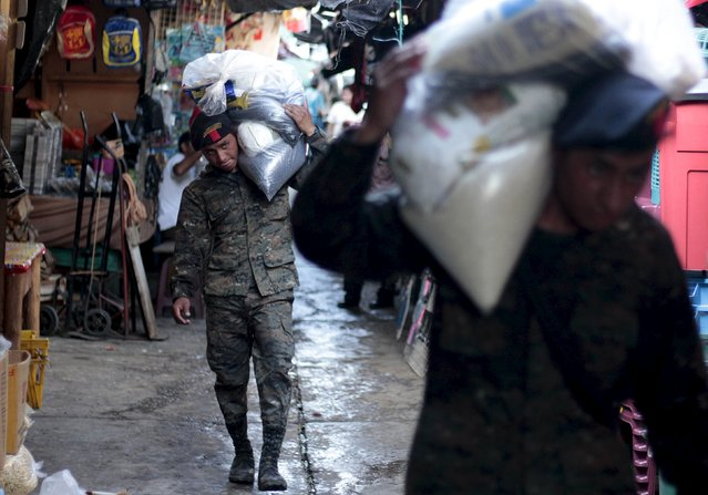 Soldiers carry food supplies for victims of heavy rains in Rio Dulce, in the Izabal region, near Guatemala City, August 8, 2015. (Photo by Josue Decavele/Reuters)